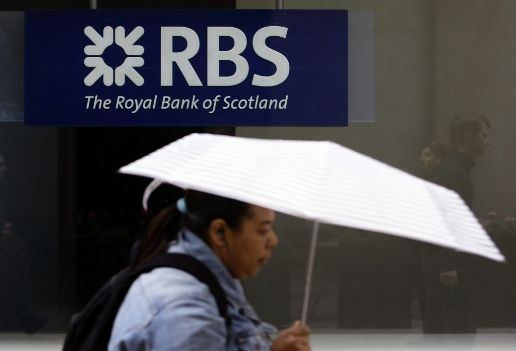 Woman passes a Royal Bank of Scotland branch in central London