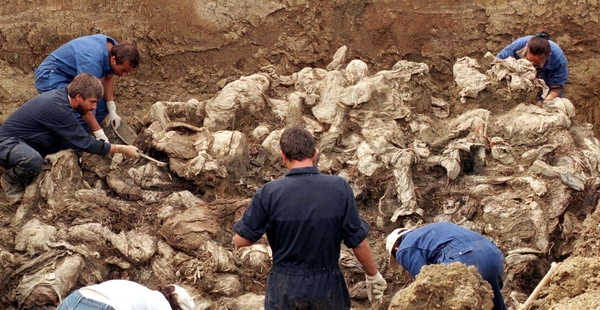 International forensic experts examine dozens of bodies, believed to be some of the 8000 missing persons who fled Srebrenica in July 1995, in a mass grave in the Serb entity of Pilicer, Bosnia in a September 18, 1996 file photo. Bosnian Serb wartime general Ratko Mladic was arrested in Serbia on May 26, 2011 after years on the run from international genocide charges, opening the way for the once-pariah state to approach the European mainstream. Mladic, accused of orchestrating the massacre of 8,000 Muslim men and boys in the town of Srebrenica and a brutal 43-month siege of Sarajevo during Bosnia's 1992-5 war, was found in a farmhouse owned by a cousin, a police official said. REUTERS/Kevin Coombs/files  (BOSNIA - Tags: CIVIL UNREST CRIME LAW) SERBIA-MLADIC/